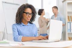 O empregado do sexo feminino está trabalhando no portátil Imagem de Stock