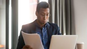 O empregado do sexo masculino preto confundido sente documentos de leitura incertos do documento fotografia de stock