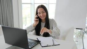 O empregado fala no secretário móvel, bonito que fala no telefone no escritório branco, gerente que da menina as cópias text no p vídeos de arquivo