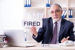 O empregado idoso farpado branco do homem de negócios infeliz com trabalho excessivo imagens de stock