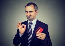 O empregado maduro do homem de negócios do mentiroso manhoso que tranquiliza seu cartão de crédito é o melhor imagem de stock