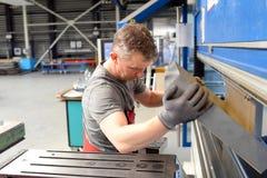 O empregado opera a máquina de dobra em uma empresa metalúrgica - seja Fotos de Stock