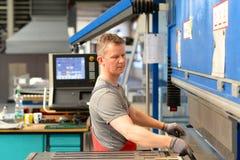 O empregado opera a máquina de dobra em uma empresa metalúrgica - seja Foto de Stock