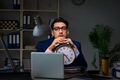 O empregado que fica tarde para terminar o trabalho no exame fotos de stock