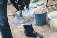 O empregado recolhe o lixo na colher da pá de pedreiro da construção imagens de stock royalty free