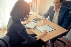 O empregador novo foi convidado a assinar o contrato de trabalho após a entrevista de trabalho imagens de stock royalty free