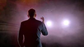 O empresário apresenta sua mostra, espalhando suas mãos aos lados O indivíduo no camisole roxo e no cilindro brilhante filme