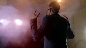 O empresário apresenta sua mostra, espalhando suas mãos aos lados O indivíduo no camisole roxo e no cilindro brilhante video estoque