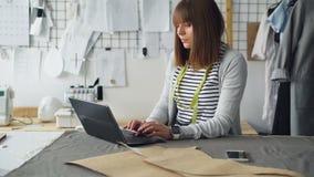 O empresário fêmea do projeto da roupa está usando o portátil para comunicar-se com seus clientes e para vender vestuários manufa vídeos de arquivo
