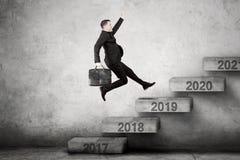 O empresário masculino escala para numerar 2019 em escadas imagens de stock