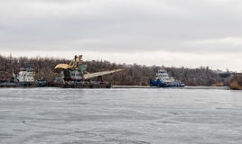 O empurrador do reboque do rio arrasta um guindaste de flutuação em um canal de navio completamente Foto de Stock