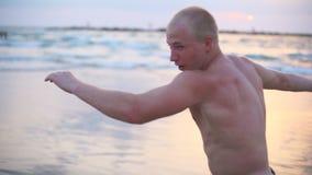 O encaixotamento praticando do homem muscular novo exercita na praia do mar O desportista masculino é autodefesa praticada apenas filme