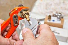 O encanador desmonta o conjunto da haste de válvula para o torneira usando o plumbin Fotos de Stock
