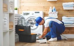 O encanador do homem de funcionamento repara a máquina de lavar na lavanderia fotos de stock
