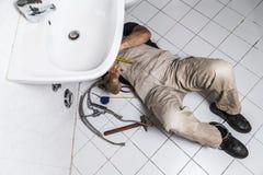 O encanador masculino do especialista repara o torneira na cozinha Foto de Stock