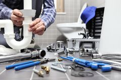 O encanador no trabalho em um banheiro, sondando o serviço de reparações, monta fotos de stock