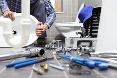 O encanador no trabalho em um banheiro, sondando o serviço de reparações, monta Fotos de Stock Royalty Free