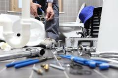 O encanador no trabalho em um banheiro, sondando o serviço de reparações, monta Fotografia de Stock Royalty Free