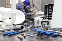 O encanador no trabalho em um banheiro, sondando o serviço de reparações, monta Imagem de Stock Royalty Free