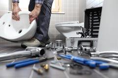 O encanador no trabalho em um banheiro, sondando o serviço de reparações, monta Imagens de Stock Royalty Free
