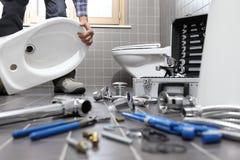 O encanador no trabalho em um banheiro, sondando o serviço de reparações, monta Imagens de Stock