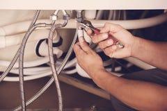 O encanador repara as tubulações Reparos masculinos do encanador do especialista fotografia de stock royalty free