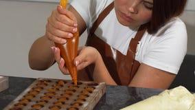 O enchimento de adição mais chocolatier fêmea novo no chocolate molda video estoque