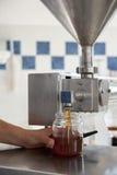 O enchimento de frascos do mel é a última etapa do processamento do mel Imagens de Stock Royalty Free
