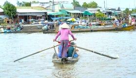 O enfileiramento do Ferryman toma visitantes através do rio ao mercado de flutuação da visita fotografia de stock