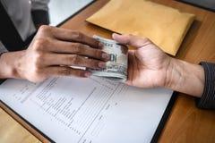 O engano desonesto no dinheiro ilegal do negócio, homem de negócios recebe o dinheiro do subôrno aos executivos para dar a sucess fotografia de stock