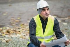 O engenheiro civil que veste um capacete branco protetor que verifica o escritório blueprints no canteiro de obras Foco seletivo imagens de stock royalty free