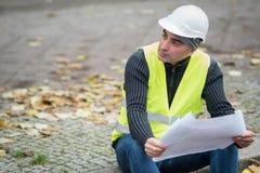 O engenheiro civil que veste um capacete branco protetor que verifica o escritório blueprints no canteiro de obras Foco seletivo foto de stock