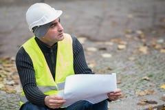 O engenheiro civil que veste um capacete branco protetor que verifica o escritório blueprints no canteiro de obras Foco seletivo fotografia de stock