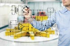 O engenheiro eletrotécnico tira um diagrama de um circuito imagens de stock