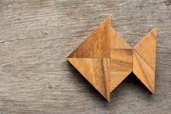 O enigma chinês do tangram nos peixes dá forma no fundo de madeira fotografia de stock royalty free