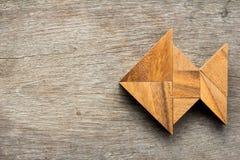 O enigma chinês do tangram nos peixes dá forma no fundo de madeira imagem de stock royalty free