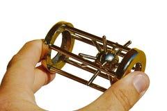 O enigma mecânico pontudo protagoniza na gaiola de aço realizada na mão esquerda no fundo branco Fotos de Stock Royalty Free