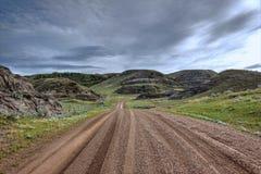 O enrolamento molhado da estrada do cascalho através da grama cobriu montes sob o céu tormentoso Foto de Stock Royalty Free