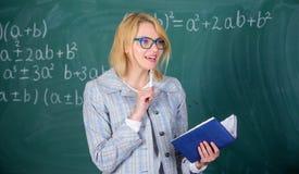 O ensino eficaz envolve adquirir o conhecimento relevante sobre estudantes Mulher do professor para explicar perto do quadro O qu imagem de stock