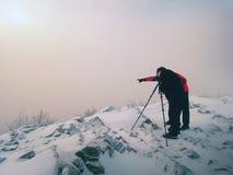 O entusiasta do caminhante e da foto fica no pico nevado no tripé Homens no penhasco que fala e que pensa foto de stock
