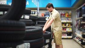 O entusiasta do carro que escolhe pneus na alameda para seu carro Homem que olha com cuidado filme