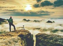 O entusiasta feliz da foto aprecia a fotografia no penhasco na rocha foto de stock royalty free