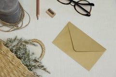 O envelope amarelo, a bandeja de madeira & o apontador, vela, espetáculos, cesta com flores imagem de stock royalty free