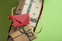 O envelope vermelho grampeado no punho de um completo dos presentes ensaca alto imagens de stock