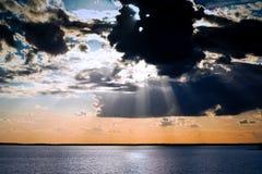 O enxame preto grande e muitas nuvens cobrem o sol, os raios de luz solar espalhados através do céu imagens de stock royalty free