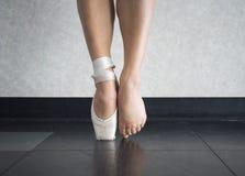O equilíbrio do ` s do dançarino de bailado em suas sapatas do pointe, e os pés atrás delas Imagens de Stock