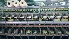 O equipamento automatizado funciona em uma fábrica, bobinando linhas em clews filme