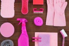 O equipamento cor-de-rosa da limpeza da cor arranjou no assoalho de madeira Fotos de Stock Royalty Free