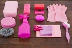 O equipamento cor-de-rosa da limpeza da cor arranjou no assoalho de madeira Fotografia de Stock