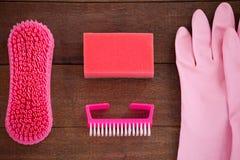 O equipamento cor-de-rosa da limpeza da cor arranjou no assoalho de madeira Foto de Stock